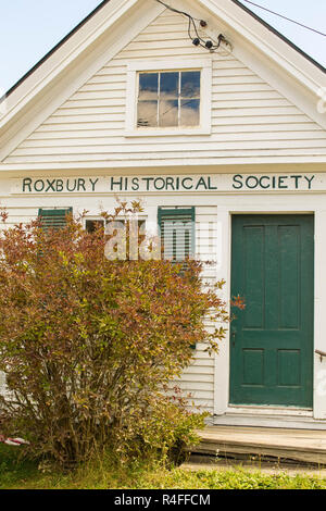Old white clapboard building with green door and shutters. Autumn. Downtown in very rural Roxbury Vermont. In the middle of nowhere, on main road. - Stock Photo