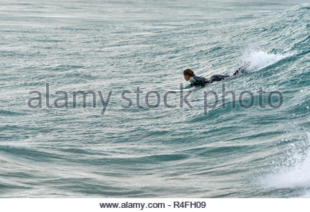A young woman in a wetsuit, kicking and paddling her surfboard onto a wave during a period of nice swell - surfing at Turners Beach, Yamba, Australia. - Stock Photo