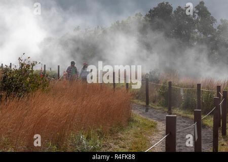 Hawaii Volcanoes National Park, Hawaii - Hikers on a trail at the edge of the Kilauea volcano. The steam comes from the volcano's steam vents. - Stock Photo