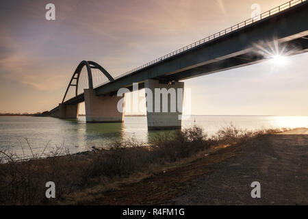 Fehmarn Sound Bridge in sunset (German: Fehmarnsundbrücke), suspension bridge with steel arches connecting the German mainland with the island in the