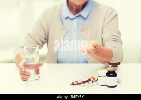 close up of senior woman with water and pills - Stock Photo
