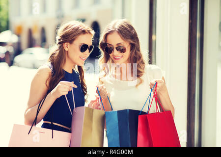 happy women with shopping bags in city - Stock Photo