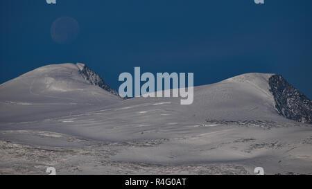 full moon sets over peak of glaciated Mt. Grossvenediger at Hohe Tauern national park, Austria - Stock Photo