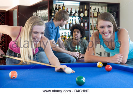 A group of teenage friends playing pool in a bar - Stock Photo