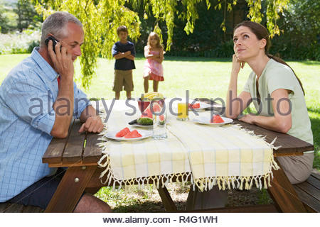 A father receiving a business call during a family lunch in the garden - Stock Photo