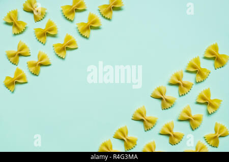 Textured Italian food background, uncooked pasta on pastel background. Top view flat lay.Menu design.Raw macaroni with copy space.raw spilled Italian pasta. Diet and food concept. - Stock Photo