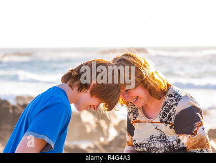 mother and son enjoy the afternoon sun at the beach - Stock Photo