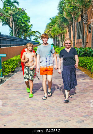 mother with two sons on the way to the beach - Stock Photo