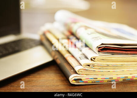 Newspapers and laptop. Pile of daily papers with news on computer. Pages with headlines, articles folded and stacked on keypad of electronic device - Stock Photo
