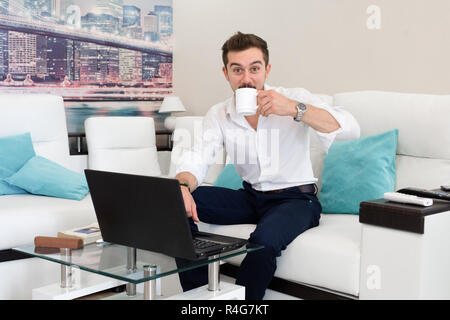 Happy young man, wearing glasses and smiling, as he works on his laptop to get all his business done early in the morning with his cup of coffee. - Stock Photo