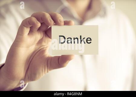 Businessman holding message card DANKE written in German - translation : THANK YOU - Stock Photo