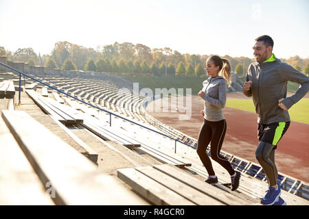 happy couple running upstairs on stadium - Stock Photo