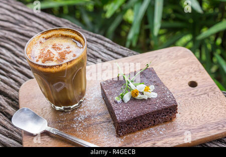 Latte Coffee and Chocolate Brownie Cake on Cutting Board on Wood Table on Tree Background. Latte coffee break time for food and drink category - Stock Photo