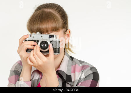 The girl photographer photographing the old film camera - Stock Photo