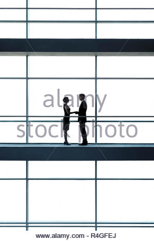 A businessman and woman on a walkway of a large modern office building, shaking hands - Stock Photo