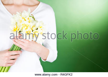 A young woman holding a bunch of daffodils - Stock Photo