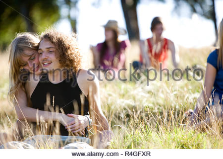A young couple sitting in a park embracing, young people in the background - Stock Photo