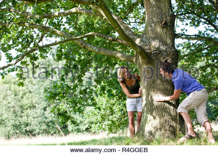 A middle aged couple playing hide and seek - Stock Photo
