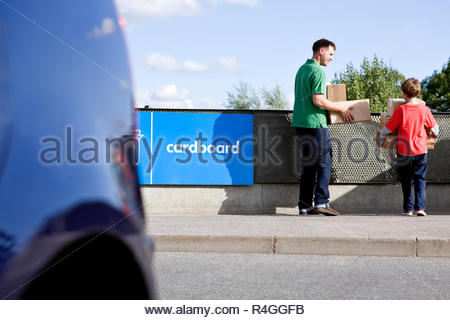 A son helping his father recycle cardboard boxes, rear view - Stock Photo