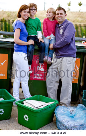 A family standing next to recycling bins - Stock Photo