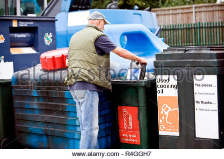 A senior man recycling an empty oil container - Stock Photo