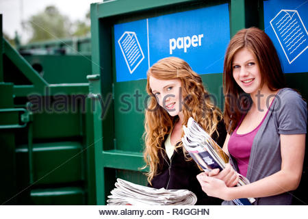 Two teenage girls standing next to a recycling container for paper - Stock Photo