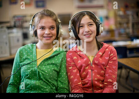 Two teenage girls sitting next to each other in a classroom wearing headphones. - Stock Photo