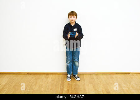 boy is playing a handgame with a band in a museum for modern Art, he enjoys it - Stock Photo