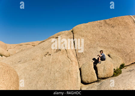 boy sitting on a rock - Stock Photo