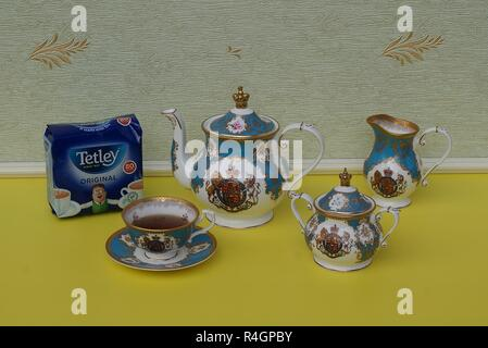 A package of original English Tetley's teabags next an English teacup with saucer, teapot, sugar bowl and cream jug, fine bone china porcelain - Stock Photo