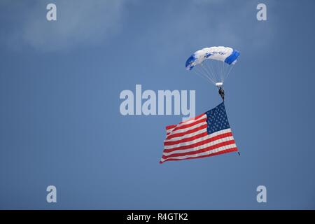 A member of the U.S. Air Force Academy Wings of Blue parachute team glides down with an American flag during the Thunder Over the Rock Air and Space Show at Little Rock Air Force Base, Arkansas, Oct. 27, 2018. In addition to the parachute team, the air show had many aerial performances such as a World War II demonstration, the U.S. Army Golden Knights and the U.S. Air Force Thunderbirds. - Stock Photo