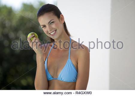 A woman in a bikini eating an apple - Stock Photo