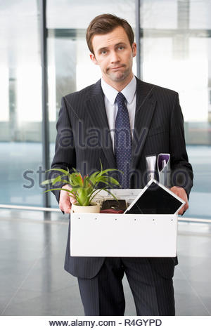 A redundant businessman taking his belongings home in a box - Stock Photo
