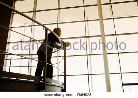 A businessman looking over balcony railings in a modern office building - Stock Photo