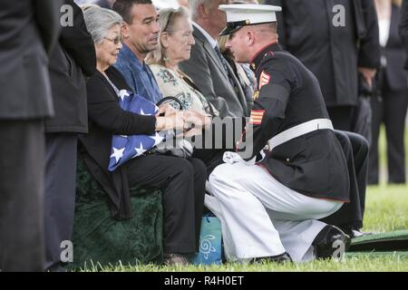 Amy House, spouse of U.S. Marine Corps Capt. John House, received the U.S. flag during Capt. House's funeral in Section 60 of Arlington National Cemetery, Arlington, Virginia, Sept. 27, 2018.  House was part of a group burial repatriation with Lance Cpl. John Killen, III; Cpl. Glyn Runnels, Jr.; and Lance Cpl. Merlin Allen, all U.S. Marine Corps, as well as U.S. Navy Hospital Corpsman Michael Judd.     From the Defense POW/MIA Accounting Agency news release: On June 30, 1967, House was the pilot of a CH-46A Sea Knight helicopter, who with three other crew members, was attempting to insert eigh - Stock Photo