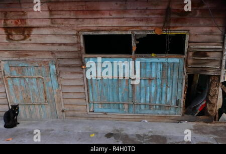 image of leaning abandoned house, it is below pavement level - Stock Photo