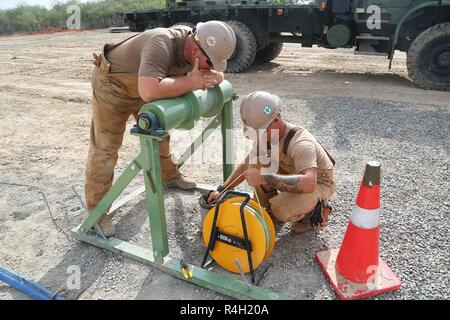 U.S. Navy Chief Equipment Operator Dennis Hill (left) and Utilitiesman 2nd Class Anthony Calleja (right), assigned to Naval Mobile Construction Battalion (NMCB) 133, tests the recharge rate of a water pump in Riohacha, Colombia, Sept. 20, 2018, during water-well drilling exploration operations as part of Southern Partnership Station 2018. Southern Partnership Station is a U.S. Southern Command-sponsored and U.S. Naval Forces Southern Command/U.S. 4th Fleet-conducted annual deployment focused on subject matter expert exchanges and building partner capacity in a variety of disciplines including  - Stock Photo