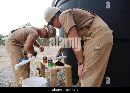 U.S. Navy Utilitiesman 2nd Class Anthony Calleja (left) and Equipment Operator Chief Dennis Hill (right), assigned to Naval Mobile Construction Battalion (NMCB) 133, assembles water outlet for the water storage system in Riohacha, Colombia, Sept. 27, 2018, during water-well drilling exploration operations as part of Southern Partnership Station 2018. Southern Partnership Station is a U.S. Southern Command-sponsored and U.S. Naval Forces Southern Command/U.S. 4th Fleet-conducted annual deployment focused on subject matter expert exchanges and building partner capacity in a variety of discipline - Stock Photo