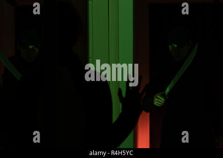 Photo of thief with machete and man with hands up in room with green light - Stock Photo