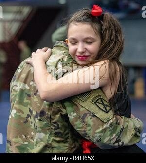 A Soldier with 1st Battalion, 32nd Infantry Regiment, 1st Brigade Combat Team, 10th Mountain Division (LI) hugs a family member after a welcome home ceremony held in 1-32IN's honor after redeploying from Djibouti at Magrath Sports Complex, Fort Drum, N.Y., Oct. 2, 2018. - Stock Photo