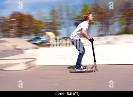 boy riding with speed on his scooter - Stock Photo