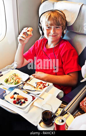 boy enjoys the dinner in the aircraft - Stock Photo