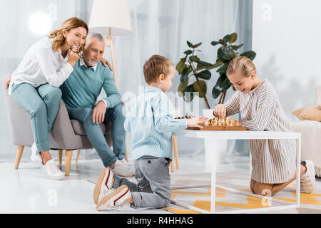 smiling kids playing chess while their grandparents sitting near at home - Stock Photo