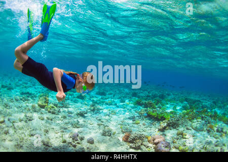 Happy little kid in snorkeling mask dive underwater with tropical fishes in coral reef sea lagoon. Family travel lifestyle in summer adventure camp. - Stock Photo