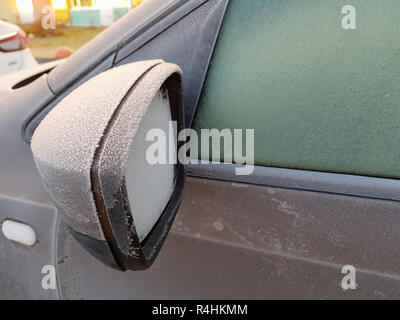 The icy mirror of the car was covered with - Stock Photo
