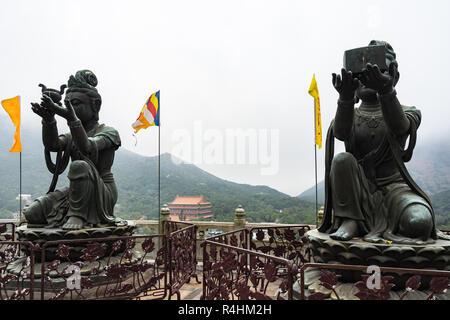 Buddhist statues making offerings to the Tian Tan Buddha (Big Buddha) with Po Lin Monastery in the background, Lantau Island, Hong Kong - Stock Photo