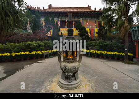 A decorated urn with burning incense sticks in the inner courtyard f Po Lin Monastery, Hong Kong, Ngong Ping, Lantau Island - Stock Photo