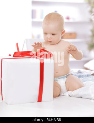 surprised baby playing with gift boxes. photo with copy space - Stock Photo