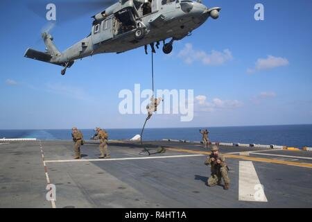A Reconnaissance Marine with the 31st Marine Expeditionary Unit's Amphibious Reconnaissance Platoon fast-ropes from an MH-60S Seahawk during Visit, Board, Search and Seizure training aboard the amphibious assault ship USS Wasp (LHD 1), while underway in the South China Sea, Sept. 29, 2018. During the training, ARP Marines refined their fast rope capabilities while Marines with the Security Platoon held aerial security to help simulate a VBSS mission. The 31st MEU, the Marine Corps' only continuously forward-deployed MEU, provides a flexible force ready to perform a wide-range of military opera - Stock Photo