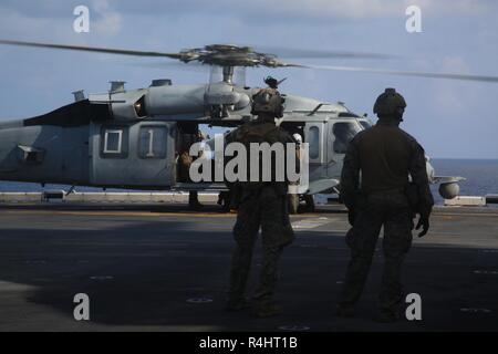 Reconnaissance Marines with the 31st Marine Expeditionary Unit's Amphibious Reconnaissance Platoon watch an MH-60S Seahawk prepare for takeoff during Visit, Board, Search and Seizure training aboard the amphibious assault ship USS Wasp (LHD 1), while underway in the South China Sea, Sept. 29, 2018. During the training, ARP Marines refined their fast rope capabilities while Marines with the Security Platoon held aerial security to help simulate a VBSS mission. The 31st MEU, the Marine Corps' only continuously forward-deployed MEU, provides a flexible force ready to perform a wide-range of milit - Stock Photo